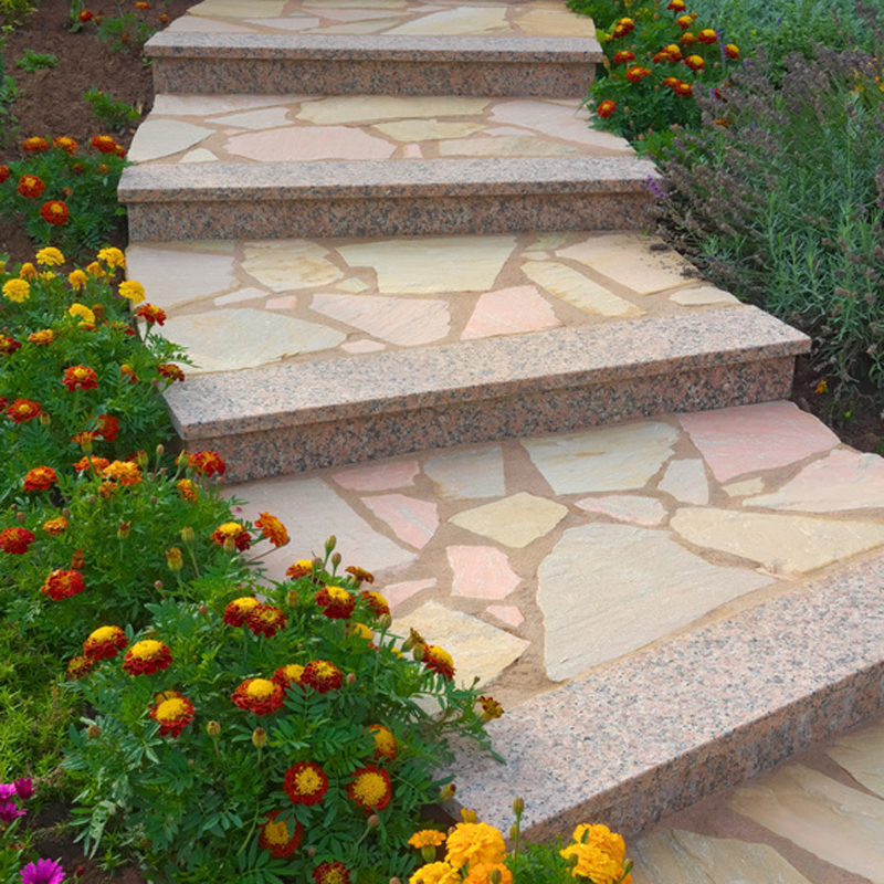 Schöne Natursteintreppe im blühenden Vorgarten